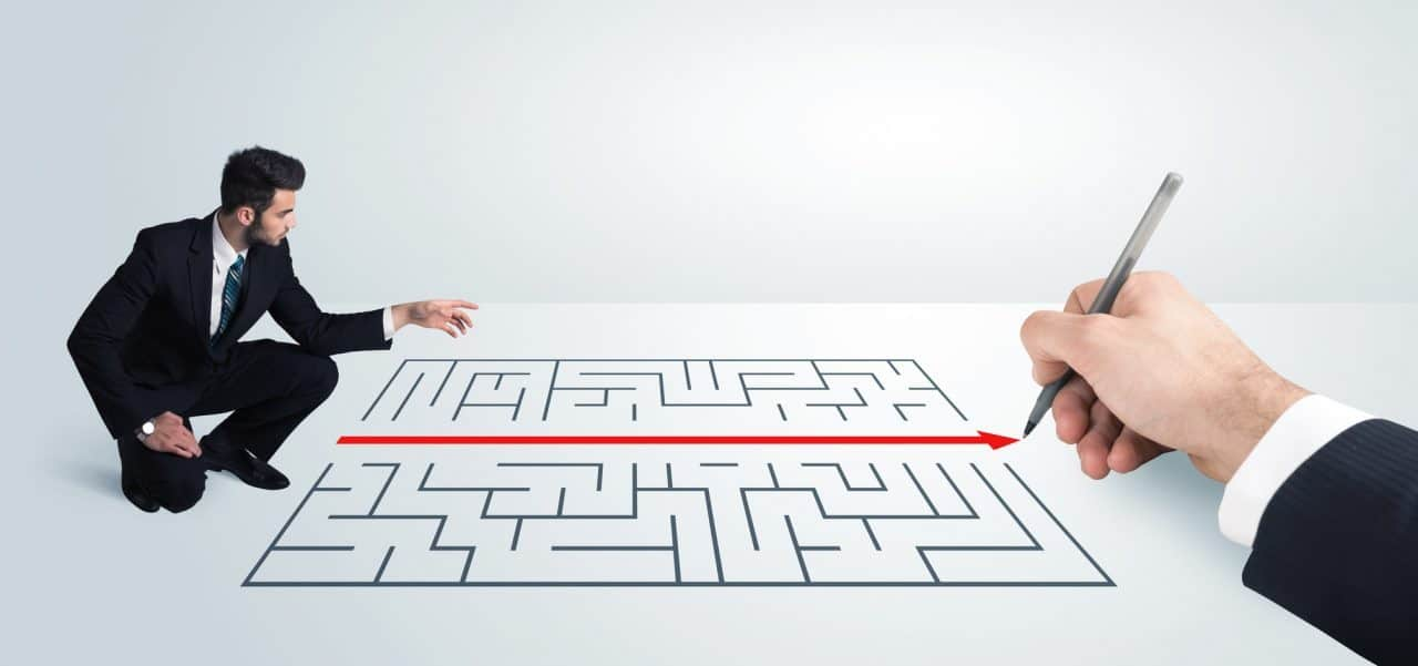 Business man looking at hand drawing solution for maze