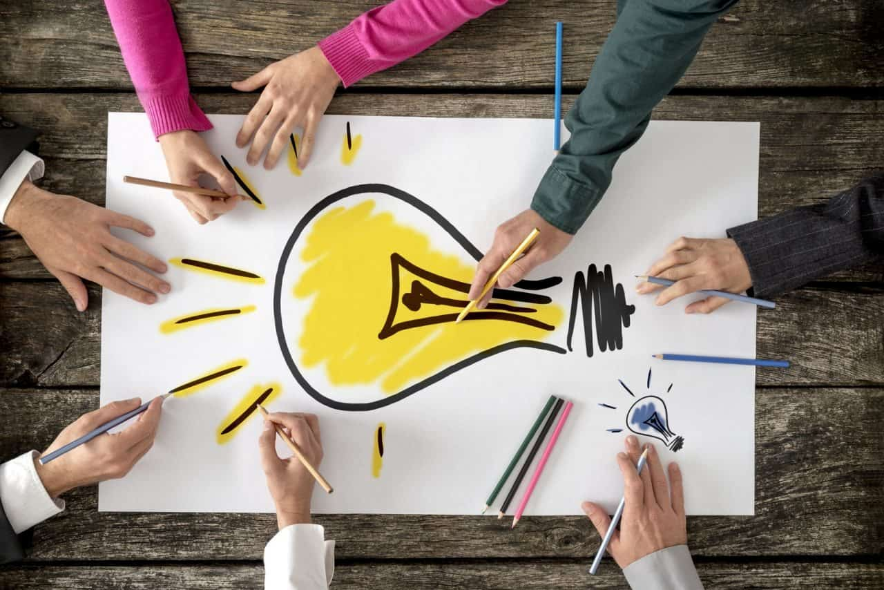 Top view of six people, men and women, drawing bright yellow light bulb on a large sheet of paper or placard. Conceptual of teamwork, research, education and innovation.